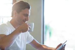 Man using digital tablet while having cup of coffee Royalty Free Stock Image