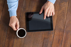 Man using digital tablet while having cup of coffee Royalty Free Stock Photography