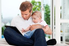 Man Using Digital Tablet while Holding Child Royalty Free Stock Photography