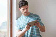 Man Using Digital Tablet At Home Stock Photo