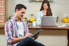 Man using digital tablet in kitchen Stock Photos