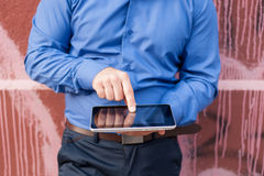 Man using digital tablet and leaning on wall outdoors. Man use digital tablet and leaning on wall outdoors and pointing touchscreen with index finger Stock Photo