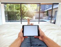 Man using digital tablet while lying on bed Stock Photos