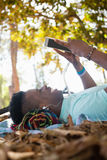 Man using digital tablet while lying on a picnic blanket Royalty Free Stock Image