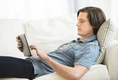Man Using Digital Tablet While Lying On Sofa Stock Images