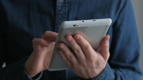 Man using digital tablet. Man in denim shirt typing on a white digital tablet, close-up stock footage