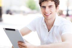 Man using digital tablet outdoors Stock Photo