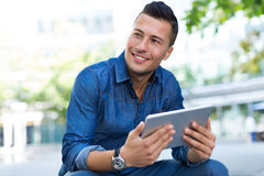 Man using digital tablet outdoors Stock Photography