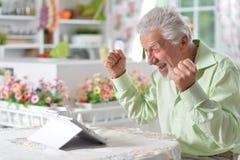 Man  using digital tablet. Portrait of a happy senior man using digital tablet Royalty Free Stock Images