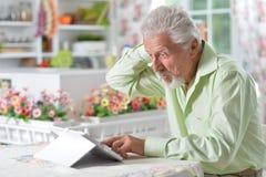 Man  using digital tablet. Portrait of a happy senior man using digital tablet Stock Image