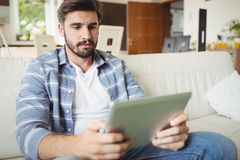 Man using digital tablet while relaxing on sofa Stock Photography