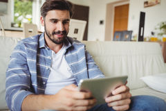 Man using digital tablet while relaxing on sofa Stock Photos