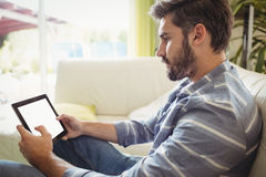Man using digital tablet while relaxing on sofa Royalty Free Stock Photos