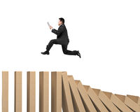 Man using digital tablet running on falling wooden dominos Stock Photography