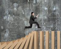 Man using digital tablet running on falling wooden dominos Royalty Free Stock Image