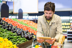 Man using digital tablet while shopping Royalty Free Stock Images