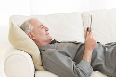 Man Using Digital Tablet On Sofa At Home Royalty Free Stock Photography
