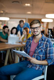 Man using digital tablet while team working in background Royalty Free Stock Photo