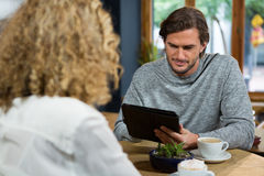 Man using digital tablet with woman in foreground at coffee house. Young man using digital tablet with woman in foreground at coffee house Royalty Free Stock Photography