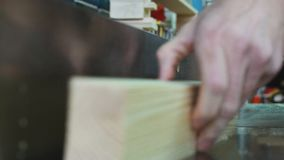 Workman in joinery workshop. Man using drill press to drill a hole into a piece of wood stock video