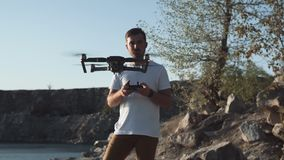 Man using drone on shore. Man using black quadcopter while standing on river shore with remote controller stock video