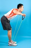 Man using elastic exercise tubing in strengthening Royalty Free Stock Photos