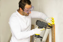 Man using an electric nail gun Stock Images