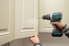 Man Using Electronic Drill To Install A Cabinet Stock Images