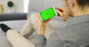 Man using green screen of smartphone. Man using empty green screen of smartphone sitting at home sofa, chroma key stock footage