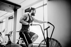 Young man using exercise bike at the gym. Fitness male using air bike for cardio workout at crossfit gym. Man using exercise bike at the gym. Fitness male using Stock Images