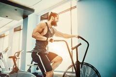 Young man using exercise bike at the gym. Fitness male using air bike for cardio workout at crossfit gym. Man using exercise bike at the gym. Fitness male using Royalty Free Stock Image