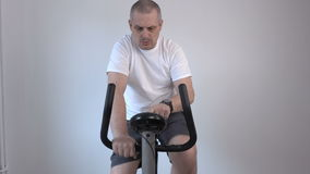 Man using exercise bike and looks at his watch stock footage
