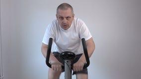 Man using exercise bike stock video