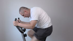 Man using exercise bike very fast stock footage