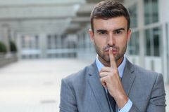 Man using a finger sign to request someone to remain silent.  stock photo