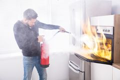 Man Using Fire Extinguisher To Stop Fire Coming From Oven. Young Man Using Red Fire Extinguisher To Stop Fire Coming From Oven In Kitchen stock photo
