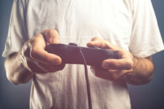Man using game pad controller to play video games. Man using game pad controller to play entertaining electronics video games, gaming and entertainment concept Royalty Free Stock Image