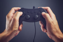 Man using game pad controller to play video games Stock Image