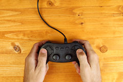 Man using game pad controller on wooden desk, top view Royalty Free Stock Photos