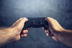 Man using gamepad controller to play video games Stock Photography