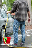 Man using garden hose for cleaning. Car royalty free stock image