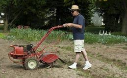 Man using a garden tiller Stock Photography