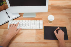 Man using graphics tablet while typing on keyboard Royalty Free Stock Image