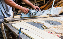 Man using a grinding machine on wood, Wood craft. Wood craft, Senior male carpenter using table saw for Shave wood at workshop Royalty Free Stock Images