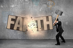 Man using hammer cracking FAITH word wooden board. Man using hammer and cracking wooden board of FAITH word, with doodles wall and concrete indoor background Royalty Free Stock Image