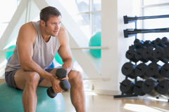 Free Man Using Hand Weights On Swiss Ball At Gym Stock Image - 7231081