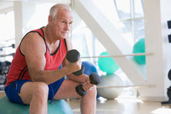 Free Man Using Hand Weights On Swiss Ball At Gym Stock Image - 7231121