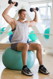 Man Using Hand Weights On Swiss Ball At Gym Royalty Free Stock Images