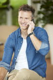 Man using handy. Shot of a middle aged man making call while sitting at home after work Stock Photo