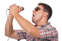 Man using headphones and singing to the microphone Stock Photos